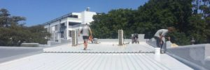 Roofers maintaining a roof.