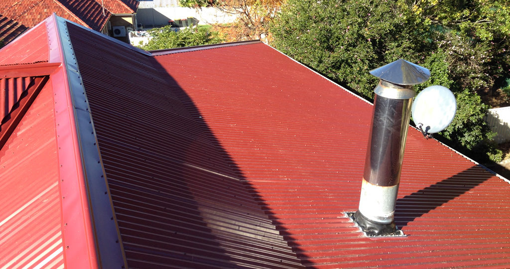 Red, steel roof with plumbing.