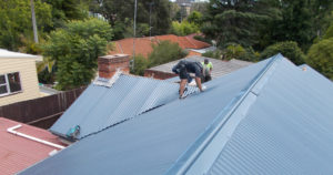 Roofers working on a metal roof.